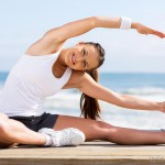 woman-in-white-top-and-shorts-stretching-near-water
